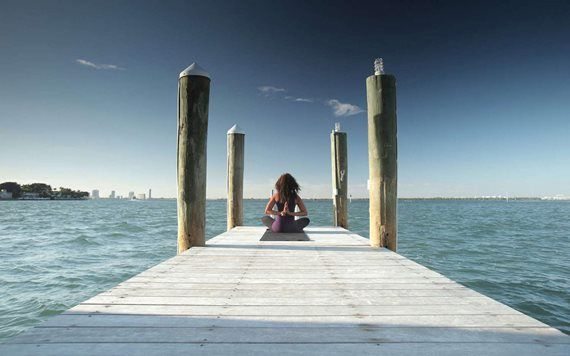 woman doing yoga on dock by water