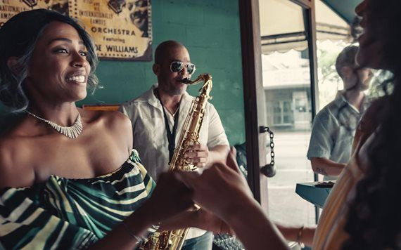 Woman smiling man playing saxophone at Ball and chain