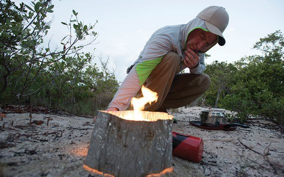 Man setting up fire in primitive campground.